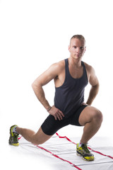 Attractive athletic young man working out with agility ladder