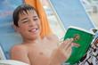 Jeune ado lisant au bord de la piscine