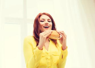 smiling young woman eating hamburger at home