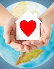 human hands holding paper house with red heart
