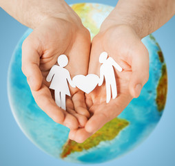 human hands holding paper couple over earth globe