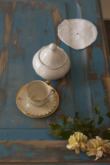 A pretty coffee cup and a sugar bowl on old wooden table