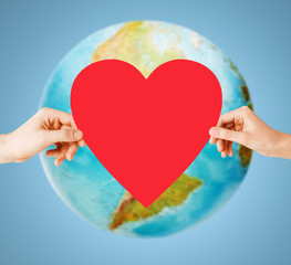human hands holding red heart over earth globe