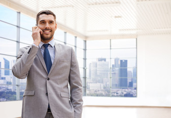 happy young businessman calling on smartphone