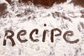 Word recipe written in white flour on  wooden table