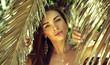 Beautiful woman between palm leaves