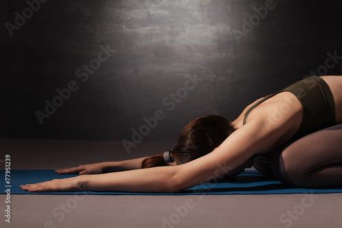 Leinwanddruck Bild Mature woman practicing yoga on the floor