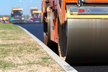 Road roller compacting asphalt near curb stone
