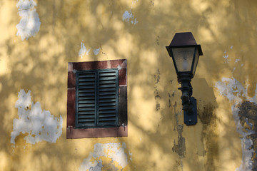 Yellow wall with window shutter and lamp