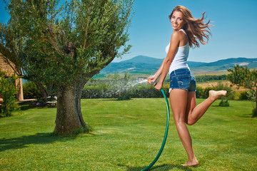 Beautiful young woman having fun in summer garden with garden ho