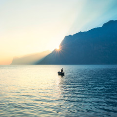 fisherman fishing in the lake under amazing sunset