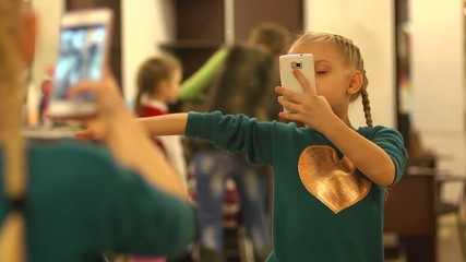 Kid girl doing selfie in a mirror
