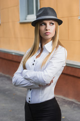 Beautiful blonde in a white blouse and a hat