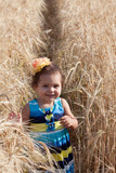 Girl's portrait on a footpath in a wheat field