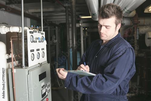Leinwanddruck Bild maintenance engineer checking technical data of heating system e