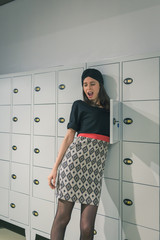 Beautiful young woman putting her arm in a locker