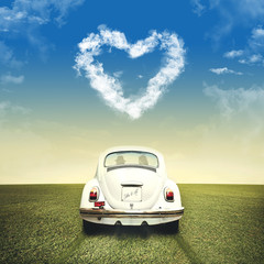 Couple driving on a white car under clouds heart shape