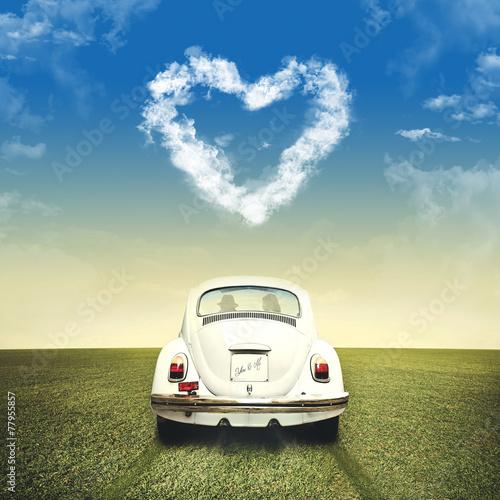 Leinwanddruck Bild Couple driving on a white car under clouds heart shape