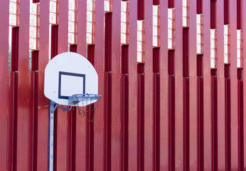 Basketball board on red metallic wall structure