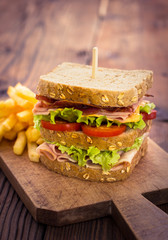 Delicious sandwich with French fries on the table
