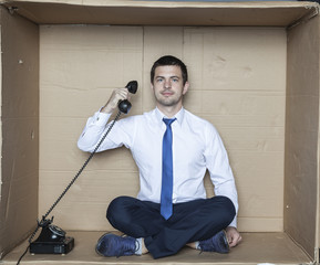 businessman hidden in a box eavesdropping phone calls