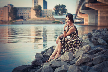 beautiful girl in dress, stones on the shore, bridge