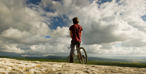 man on bicycle near a cliff with covered by forest hills