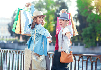 Two happy beautiful girls with shopping bags in the city