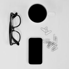 eyeglasses, smartphone, coffee and heart-shaped paperclips