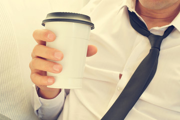 young man drinking coffee in a paper cup