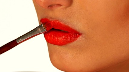 Young woman applying red lipstick by brush, close up