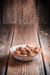 Falling cocoa powder on chocolate balls
