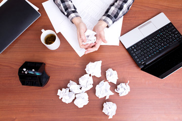 Office worker hands crumple sheets of paper at the table