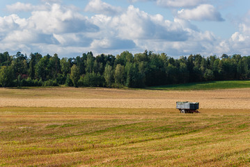 Wagon on a harvested field in a rural landscape.