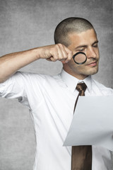 businessman with magnifying glass reading contract