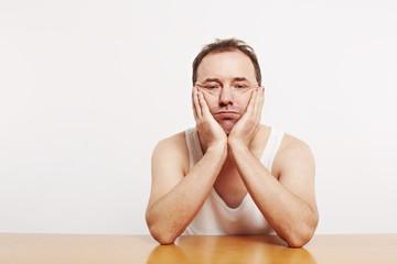Mann stützt sich mit dem Armen den Kopf, am Tisch 2