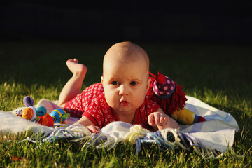 Adorable baby girl lying on green summer lawn
