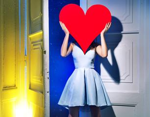 Woman hiding herself behind a heart
