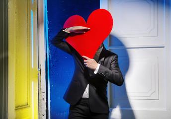 Cheerful man hiding himself behind a heart