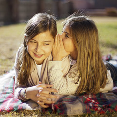 Niña contando secreto a su hermana