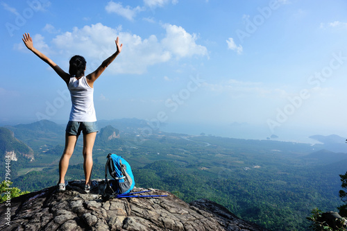 strong confident woman hiker open arms at on mountain peak rock - 77964484