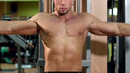 Muscular man training his hands in the gym