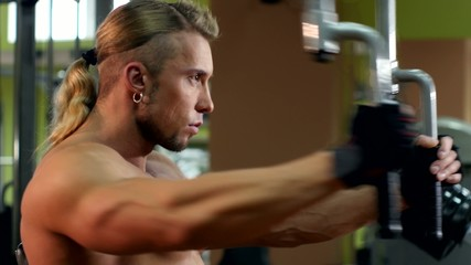 Stylish muscular man training his hands in the gym, slow motion