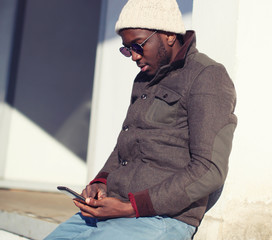 Lifestyle portrait of stylish young african man using smartphone