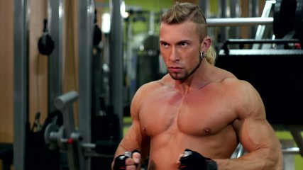 Muscular man training and using pull the lower unit in gym, cam