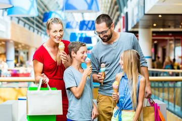 Familie in Einkaufszentrum beim einkaufen mit Tüten