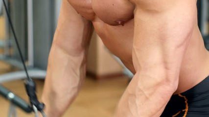 Handsome, muscular sportsman doing weight lifting press lower