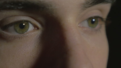 4k UHD - Close-up of a young man eyes in the dark