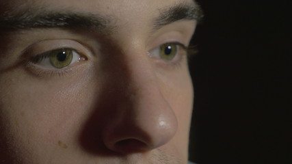 Close-up of a young man eyes in the dark watching TV