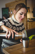 Portrait of woman in sweater pouring coffee from thermos in cup